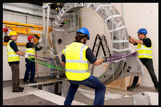 Electricians moving on a large cylinder.