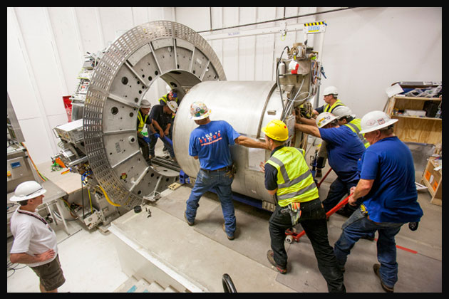 Electricians working on a large cylinder.